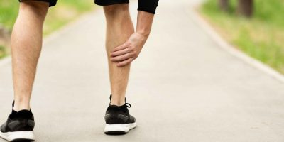 Male runner is suffering from calf leg pain or sprain on jogging, holding sore and painful muscle, free space